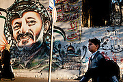 A young boy walks past a mural of Yasser Arafat in the Rimal District of Gaza City.