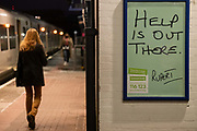 A female rail traveller walks along the platform at Loughborough Junction railway station where a Samaritans poster urges those with mental health issues, or even thoughts of suicide, to seek help from the registered charity aimed at providing emotional support to anyone in emotional distress, struggling to cope, or at risk of suicide throughout the United Kingdom and Ireland, often through their telephone helpline, on 27th February 2021, in London, England.