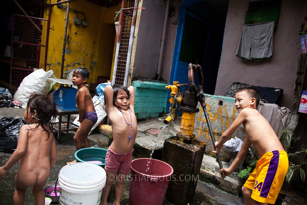 Children play at a water pump while they fetch water for the house. Most houses in the slums in Manila do not have running water or any sanitation.