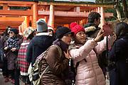 Tourists taking selfies at the Fushimi Inari Taisha. Kyoto, Japan