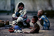 """Ration card clutched in her left hand, a mother and her three hungry children wait for powdered milk donated by the United States and Canada to be dispensed by the Dutch Red Cross ¾ another mind-numbing scene in Bangladesh in 1974. International relief experts called Bangladesh the most underfed and overcrowded nation in the world, while The New York Times reported, """"Mass hunger and starvation is no longer a threat. It is here.""""  © Steve Raymer / National Geographic Creative"""