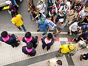 """14 JULY 2013 - BANGKOK, THAILAND:  Anti-government protesters walks past of line of riot police during a protest Sunday. About 150 members of the so called """"White Mask"""" movement marched through the central shopping district of Bangkok Sunday to call for the resignation of Yingluck Shinawatra, the Prime Minister of Thailand. The White Mask protesters are strong supporters of the Thai monarchy. They claim that Yingluck is acting as a puppet for her brother, former Prime Minister Thaksin Shinawatra, who was deposed by a military coup in 2006 and now lives in exile in Dubai.       PHOTO BY JACK KURTZ"""