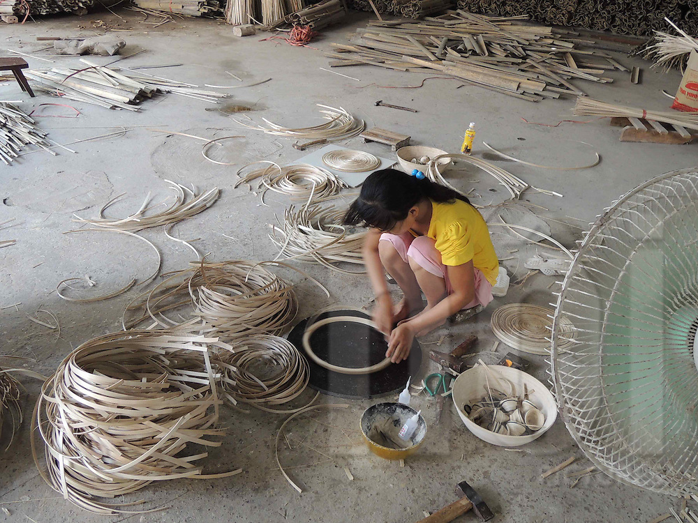 Young Vietnamese girl makes bowls from bamboo in a workshop in Cat Dang village, Vietnam, Southeast Asia