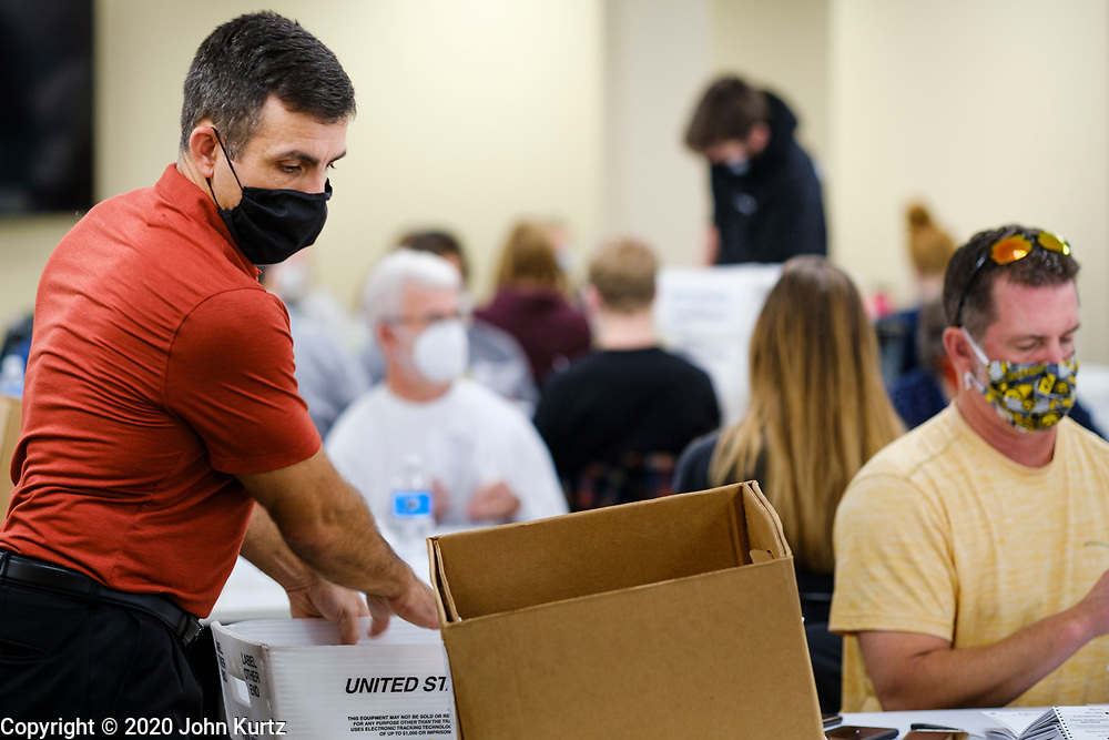 02 NOVEMBER 2020 - DES MOINES, IOWA: An election worker collects opened and sorted mail in ballots at the Polk County Auditor's Office in Des Moines Monday. Officials started opening mail in ballots Monday morning but won't start counting ballots until Tuesday morning. This is the last day of early voting before the 2020 US presidential election. The line to vote at the Polk County Auditor's Office was 4 blocks long Monday morning. An elections official said that by November 3, which is Election Day, about 45 percent of the registered voters in Polk County will have already voted.     PHOTO BY JACK KURTZ