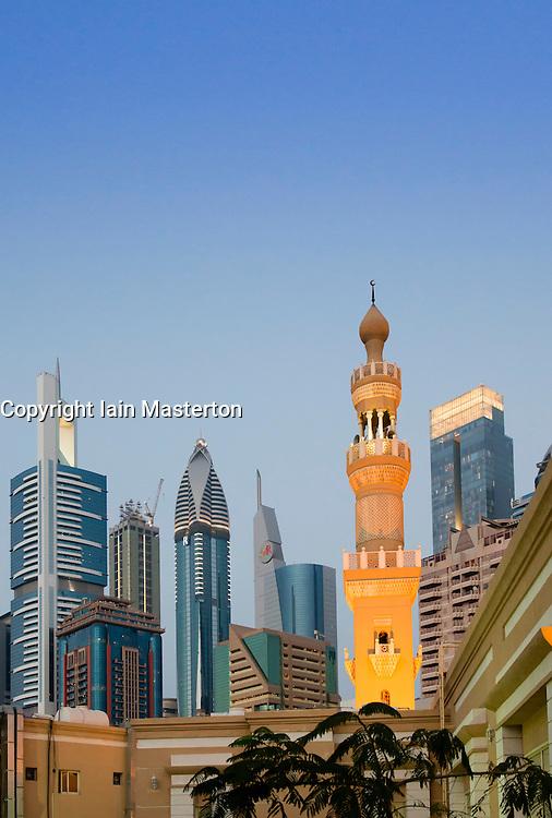 Mosque minarets and skyline of skyscrapers in Dubai United Arab Emirates UAE