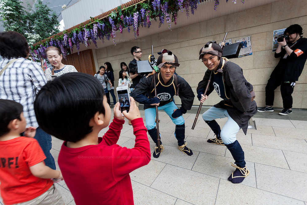 Kids take a photo of actors dressed as characters from the Edo (samurai) Period to welcome visitors to Haneda International Airport, Tokyo, Japan. Tuesday May 3rd 2016. The Edo festival takes place over the three days of national holidays called Golden Week ( May 3rd to 5th) and features costume parades, music and stage shows along with other fun activities for visitors in and around the Edo themed shopping areas in the terminal building.