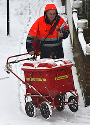 © Licensed to London News Pictures. 18/01/2013. London, UK A postman delivers post in snow is a residential street in West London today 18th January 2013. Photo credit : Stephen Simpson/LNP