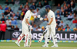 England's Joe Root and Dawid Malan touch gloves after a DRS decision went in their favour during day four of the Ashes Test match at the Adelaide Oval, Adelaide.