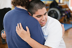 Boy with physical and learning disabilities hugging a member of staff at his school,