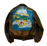 """This type A-2 flight jacket belonged to Calvin E. McCart, a tail gunner attached to the 570th squadron of the 390th Bomb Group. On the front left of the jacket is the 570th squadron insignia patch, a joker with 4 aces behind it. The name """"Mac"""" is painted on the front right of the jacket, a man parachuting is painted below the name. McCart flew 35 successful missions over Europe, this is signified by the 35 bombs painted on the sleeves of his jacket. The name """"Shuttle-Babe"""" is painted on the back of the jacket above artwork. The artwork on the back of the jacket is a B-17 flying through the clouds with the 8th Air Force logo behind the plane. Throughout the course of his 35 missions McCart survived 3 emergency landings."""