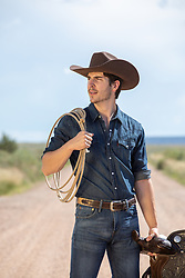 cowboy with a lasso and saddle on a dirt road