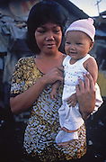 In the Tondo slum in Manila, a young Filipino mother holds her healthy-looking baby.