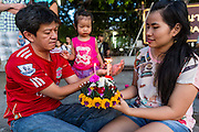 "17 NOVEMBER 2013 - BANGKOK, THAILAND: A family prays before floating their krathong in the Chao Phraya River at Wat Yannawa on Loy Krathong in Bangkok. Loy Krathong (also written as Loi Krathong) is celebrated annually throughout Thailand and certain parts of Laos and Burma (in Shan State). The name could be translated ""Floating Crown"" or ""Floating Decoration"" and comes from the tradition of making buoyant decorations which are then floated on a river. Loi Krathong takes place on the evening of the full moon of the 12th month in the traditional and they do this all evening on the 12th month Thai lunar calendar. In the western calendar this usually falls in November. The candle venerates the Buddha with light, while the krathong's floating symbolizes letting go of all one's hatred, anger, and defilements       PHOTO BY JACK KURTZ"
