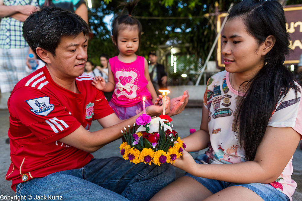 """17 NOVEMBER 2013 - BANGKOK, THAILAND: A family prays before floating their krathong in the Chao Phraya River at Wat Yannawa on Loy Krathong in Bangkok. Loy Krathong (also written as Loi Krathong) is celebrated annually throughout Thailand and certain parts of Laos and Burma (in Shan State). The name could be translated """"Floating Crown"""" or """"Floating Decoration"""" and comes from the tradition of making buoyant decorations which are then floated on a river. Loi Krathong takes place on the evening of the full moon of the 12th month in the traditional and they do this all evening on the 12th month Thai lunar calendar. In the western calendar this usually falls in November. The candle venerates the Buddha with light, while the krathong's floating symbolizes letting go of all one's hatred, anger, and defilements       PHOTO BY JACK KURTZ"""