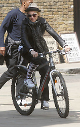 ©London News Pictures. 15/01/2011 .Picture Credit Should read Neil Hall/London News Pictures.Madonna directs her new period film W.E. starring Abbie Cornish about the abdication of King Edward in London ton 08/08/2010 Pictured is Madonna cycling to the set with one sock rolled up