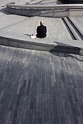 A lonely-looking man spends his lunchtime in an empty urban landscape in central London's riverside.