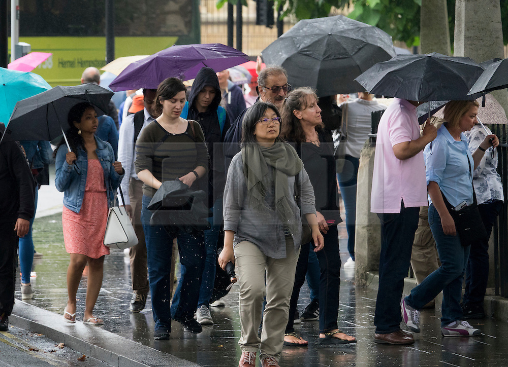 © Licensed to London News Pictures. 02/08/2016. London, UK. Visitors to Westminster Abbey carry umbrellas as intermittent rain showers hit the capital. Photo credit: Peter Macdiarmid/LNP