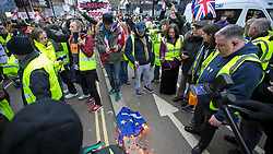 © Licensed to London News Pictures. 19/01/2019. London, UK. Yellow Vest protesters burn an EU flag while marching through central London in support of Brexit. Photo credit: George Cracknell/LNP