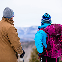 A man and woman take in the view towards the White Mountains while snowshoeing at Loon Echo Land Trust's Bald Pate Mountain Preserve in South Bridgton, Maine.