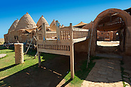 """Pictures of the beehive adobe buildings of Harran with a summer outdoor bed,  south west Anatolia, Turkey.  Harran was a major ancient city in Upper Mesopotamia whose site is near the modern village of Altınbaşak, Turkey, 24 miles (44 kilometers) southeast of Şanlıurfa. The location is in a district of Şanlıurfa Province that is also named """"Harran"""". Harran is famous for its traditional 'beehive' adobe houses, constructed entirely without wood. The design of these makes them cool inside. 32 .<br /> <br /> If you prefer to buy from our ALAMY PHOTO LIBRARY  Collection visit : https://www.alamy.com/portfolio/paul-williams-funkystock/harran.html<br /> <br /> Visit our TURKEY PHOTO COLLECTIONS for more photos to download or buy as wall art prints https://funkystock.photoshelter.com/gallery-collection/3f-Pictures-of-Turkey-Turkey-Photos-Images-Fotos/C0000U.hJWkZxAbg ."""