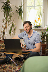 Mid adult man working on laptop in living room and smiling, Munich, Bavaria, Germany