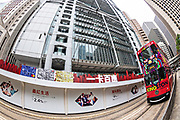 Fisheye view of a historic double decker tram traveling past the Hong Kong Shanghai Bank building in the central district of Hong Kong.