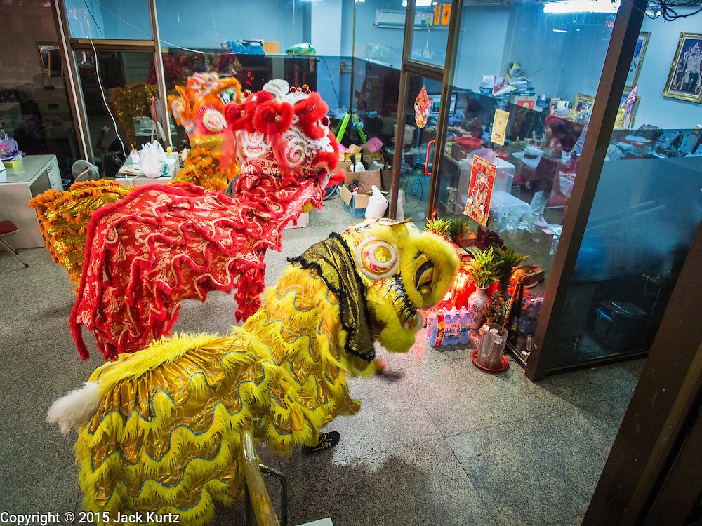 """19 FEBRUARY 2015 - BANGKOK, THAILAND: Chinese lion dancers perform for Chinese New Year in a jewelry business on Yaowarat Road in Bangkok. 2015 is the Year of Goat in the Chinese zodiac. The Goat is the eighth sign in Chinese astrology and """"8"""" is considered to be a lucky number. It symbolizes wisdom, fortune and prosperity. Ethnic Chinese make up nearly 15% of the Thai population. Chinese New Year (also called Tet or Lunar New Year) is widely celebrated in Thailand, especially in urban areas that have large Chinese populations.    PHOTO BY JACK KURTZ"""