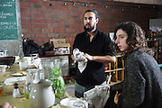 """Aladdin Charni and Gilia Bataille cofounders of Freegan Pony drying dishes.<br /><br />The Freegan Pony is an alternative restaurant housed in a squat. It was founded in 2015 by Aladdin Charni with three other collaborators. The restaurant specialises in cheap vegetarian cuisine, serving meals which guests reserve a place through a Facebook group, paying €2 a meal. The restaurant meals contain unsold and donated food, collected from wholesellers at the Paris Rungis vegetable market. The Freegan Pony is located at the Porte de la Vilette on the outskirts of Paris, at the entrance to the peripherique outer circle motorway.<br /><br />Freegans are people who employ alternative strategies for living based on limited participation in the conventional economy and minimal consumption of resources. Freeganism is the practice of reclaiming and eating food that has been discarded. People who attempt to live an ethical lifestyle by reusing trash and rubbish thrown away by others.<br /><br />Freeganism is an ill-defined activity and is a subset of the larger anti-capitalist and environmental protest movements. It embraces alternative, anti-consumerist lifestyles. Freegan practices also include co-operative living, squatting and """"freecyling"""", or matching things that people want to get rid of with things other people need"""