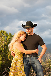 hot cowboy with a beautiful girl outdoors on a ranch