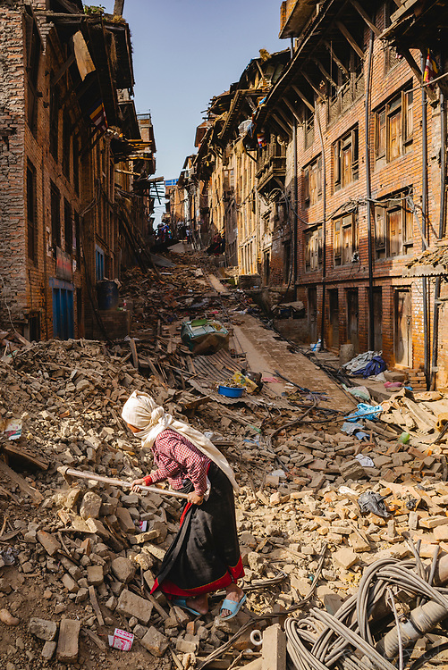 An elderly woman uses a garden hoe to search through the rubble of a house destroyed by the 2015 Nepal earthquake.