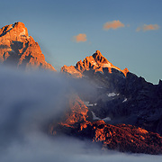 Warm light covers the peaks of the Teton range at sunrise as fog clears in the valley.