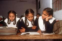 School girls sitting at desk reading books in senior secondary modern school; Punjabi University; Patiala; Punjab; India,