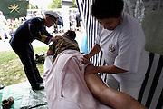 Nederland, Groesbeek, 17-7-2003<br /> De derde dag van de Nijmeegse vierdaagse, 4daagse, is traditioneel de zwaarste, met heuvels in het parcours. Massage van de benen van een militair, die een oude bekende tegenkomt. Wandelsport, grootschalig wandelevenement, wandelen, recreatie, verzorging, benen, masseuse.<br /> Foto: Flip Franssen/Hollandse Hoogte