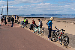 Portobello, Scotland, UK. 11 May 2020. Police patrolling promenade and beach at Portobello this afternoon in warm sunny weather. They spoke to the public who were sitting on the beach or on sea wall asking them to keep moving. Pictured;  People still sitting on wall after police leave. Iain Masterton/Alamy Live News