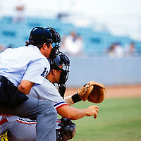 Generic baseball image of home plate umpire and catcher during the warm up for the pitcher.