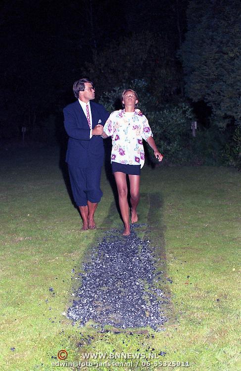 NLD/Oosterbeek/19910816 - Emile Ratelband loopt met een van zijn kinderen over vuur in de tuin van zijn huis in Oosterbeek