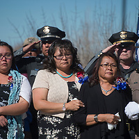 Mother of fallen Navajo Police Officer Houston Largo Maggie Charley, right, is surrounded by friends and members of the Navajo Nation Police Force as she watches her son's casket be carried in to the Rehoboth High School gym for his funeral services Thursday March 16 in Gallup.