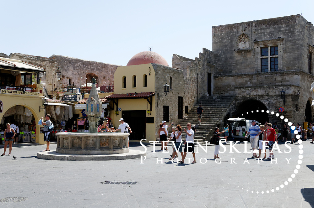 Rhodes. Greece. Ippokratous Square (Hippocrates Square) with central Turkish fountain at Rhodes Old Town. The square is situated inside the old walled town of Rhodes which is a UNESCO world heritage listed site and the best preserved, oldest and largest living medieval city in Europe.