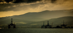 Oil rigs at sunset stand off the village of Invergordon in the Cromarty Firth, Scotland<br /> <br /> (c) Andrew Wilson | Edinburgh Elite media