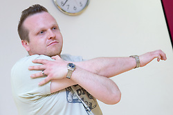 Man stretching his arms and back in an aerobics class at his sports leisure centre,