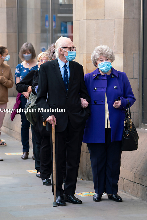 Edinburgh, Scotland, UK. 13 July, 2020, Monday in Scotland saw re-opening of shopping centres after further relaxation of coronavirus lockdown on business. John Lewis & Partners department store opened early at 9.30 am after a long queue had formed outside. Pictured; elegantly dressed senior couple in queue. Iain Masterton/Alamy Live News