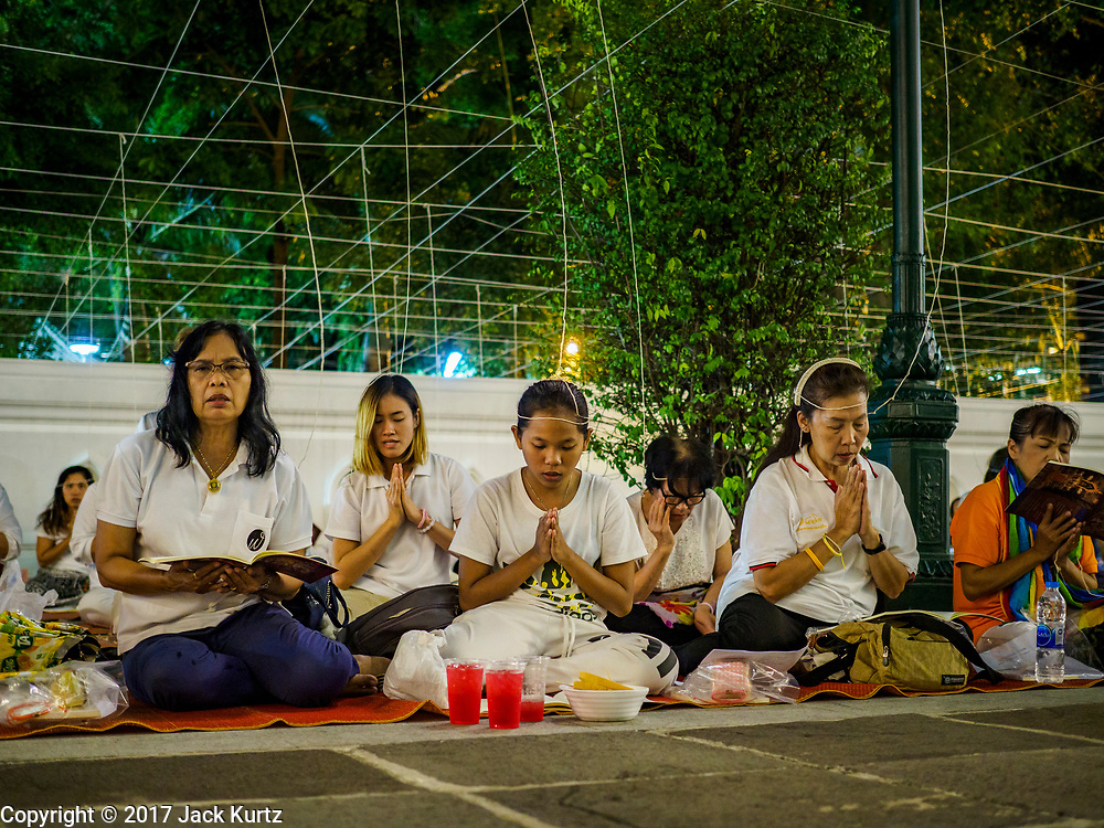 31 DECEMBER 2017 - BANGKOK, THAILAND: People participate in an overnight prayer and chanting service on New Year's Eve at Wat Pathum Wanaram in central Bangkok. The strings attached to their heads unite and amplify the prayers. Many Thais go to temples and shrines to pray and meditate during New Year's Eve and New Year's Day.    PHOTO BY JACK KURTZ
