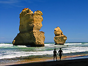 "A romantic couple walks by sea stacks ""Gog and MaGog"" at the beautiful wild beach at Gibson Steps in Port Campbell National Park, Victoria, Australia. Twelve Apostles Marine National Park protects a collection of miocene limestone rock stacks in the Indian Ocean (or Southern Ocean according to Australian geographers), offshore of the Great Ocean Road. The Great Ocean Road (B100) is a 243-km road along the southeast coast of Australia between Torquay and Warrnambool, in the state of Victoria. Dedicated to casualties of World War I, the Great Ocean Road was built by returned soldiers between 1919 and 1932 and is the world's largest war memorial. Published in ""Light Travel: Photography on the Go"" book by Tom Dempsey 2009, 2010."