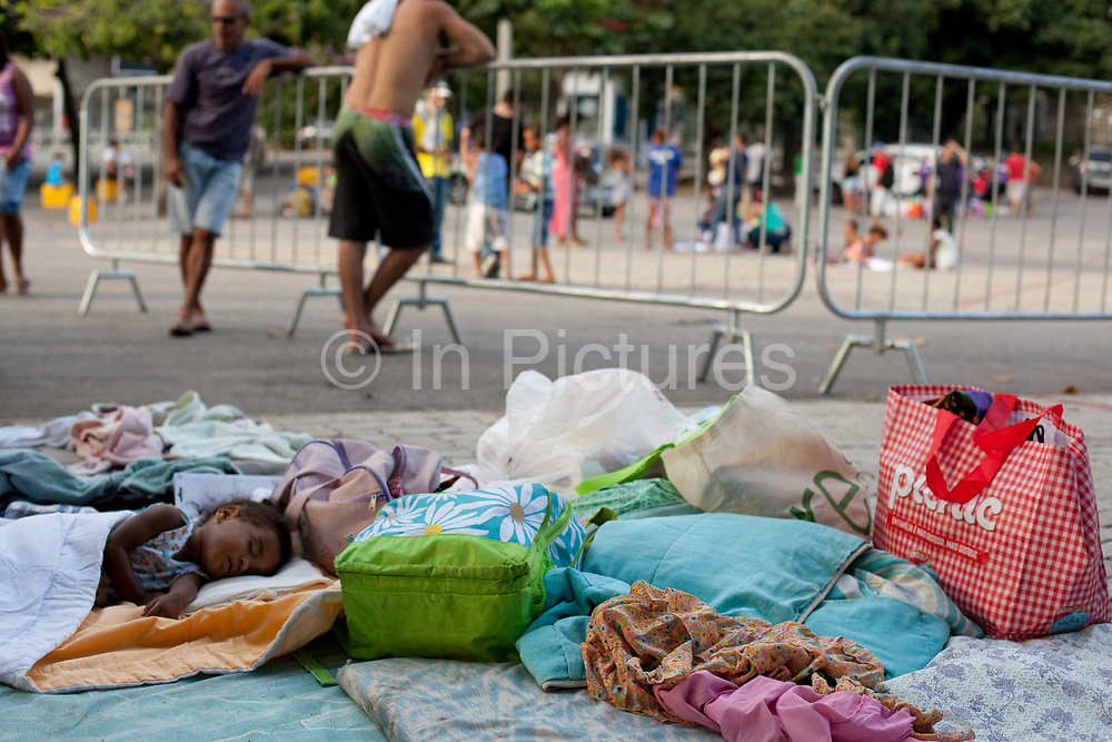 Small chilr girl sleeping on the floor in the square with blankets. In April 2014 thousands of people were evicted from Telerj favela in an old building owned by communications company Oi. Having nowhere to go, they camped outside the Central Cathderal in Rio de Janeiro, Brazil. Many of them were children, they received many donations from local people and community groups.
