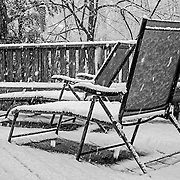I happened to look out the door and saw this scene.  There are so many aspects that make this shot fun.  The bare spots under the chairs, the contrast of summer type chairs covered in show, the snow falling, etc.  Taking this shot to black and white really helps emphasize that it was taken in winter.