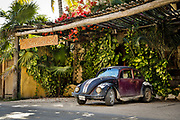 """SHOT 2/16/19 3:08:43 PM - An old VW Bug parked outside of a boutique hotel in Tulum, Mexico. The Volkswagen Beetle—officially the Volkswagen Type 1, informally in German the Käfer (meaning """"beetle""""), in parts of the English-speaking world the Volkswagen Bug, and known by many other nicknames in other languages—is a two-door, rear-engine economy car, intended for five occupants that was manufactured and marketed by German automaker Volkswagen (VW) from 1938 until 2003. Tulum (sometimes Tulum Pueblo) is the largest community in the municipality of Tulum, Quintana Roo, Mexico. It is located on the Caribbean coast of the state, near the site of the archaeological ruins of Tulum. The community had a 2010 census population of 18,233 inhabitants. As recently as the early 1990s Tulum Pueblo was a quiet village about 2 miles from the archaeological site, and tourism outside of the ruins was limited to a few small shops and simple cabanas on the beach. More recently the """"hotel zone"""" of boutique hotels along the Tulum beach has grown to more than 70 small hotels with an upscale bohemian vibe to many of the properties. (Photo by Marc Piscotty / © 2019)"""