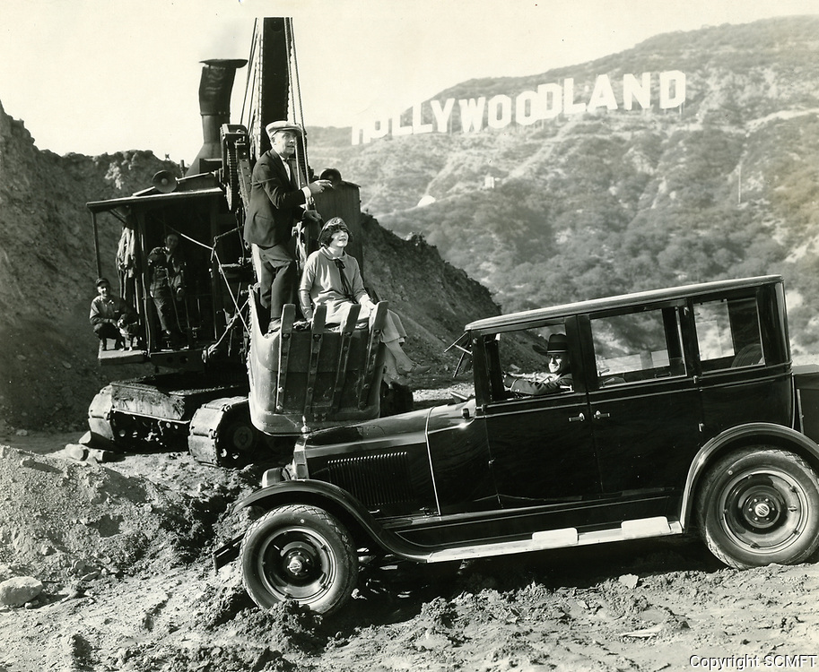 1923 Louise Glaum and Pat O'Malley on a steamshovel as their driver navigates the rough terrain near the Hollywoodland sign