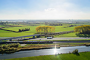 Nederland, Gelderland, Betuwe, 24-10-2013; Betuweroute, ter hoogte van Echteld. De goederenspoorlijn loopt parallel aan autosnelweg A15. De goederentrein is onderweg naar de haven van Rotterdam. Het spoor voor de gewone trein kruist de Betuwelijn, de A15 en de rivier de Linge.<br /> Betuweroute, railway from Rotterdam to Germany, near Echteld. The freight railway runs parallel to highway A15. The freight is on its way to the port of Rotterdam.<br /> luchtfoto (toeslag op standaard tarieven);<br /> aerial photo (additional fee required);<br /> copyright foto/photo Siebe Swart.