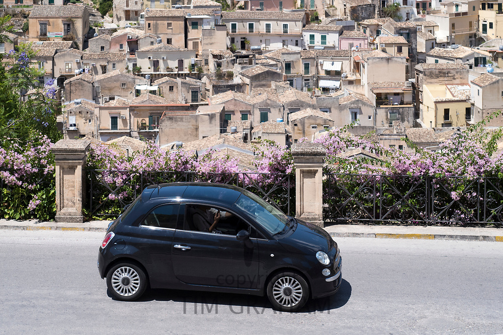 Black colour Fiat 500 Cinquecento in hill city of Modica Alta looking towards Modica Bassa, Sicily, Italy