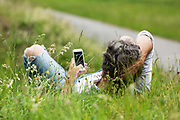 man lying on the grass with smartphone
